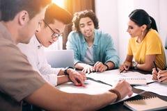 multiculturele groep bedrijfscollega's die bespreking hebben bij lijst met grafieken in modern royalty-vrije stock afbeelding