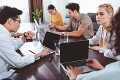 multiculturele partners die vergadering hebben bij lijst met laptops en glazen water in modern royalty-vrije stock afbeeldingen