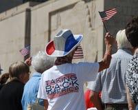 A multidão acena bandeiras americanas na reunião para fixar nossas beiras Fotos de Stock