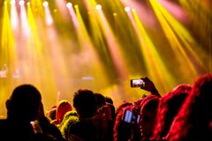 Multidão Cheering no película do festival de música, com mãos nos adolescentes do ar que têm o divertimento fotos de stock