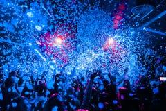 A multidão da silhueta do clube noturno entrega acima na fase do vapor dos confetes fotografia de stock royalty free