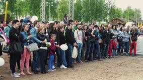 Multidão de estada dos povos na rua audiências Festival do verão Dia ensolarado Crianças filme