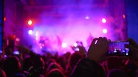 A multidão de fãs com o smartphone nas mãos aprecia a música ao vivo no concerto em luzes vívidas da fase video estoque