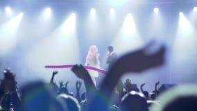 Multidão de fãs que acenam as mãos na frente da fase em concerto da noite unfocused em iluminar projetores filme