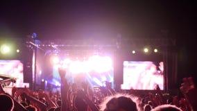 A multidão de fãs que acenam os braços e a posse telefonam com indicações digitais no concerto de rocha, muitos braços aumentados video estoque
