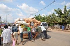 A multidão de jovens que empurram um carro sobrecarregou sacos Fotos de Stock Royalty Free