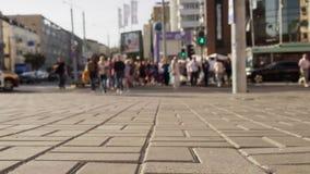 A multidão de povos atravessa ao longo da faixa de travessia a rua da cidade vídeos de arquivo