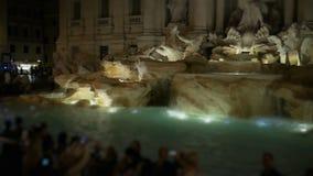 Multidão de povos com câmeras da foto e de telefones espertos perto da fonte do Trevi em Roma na noite filme