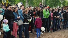 A multidão de povos fica na areia no parque audiências Festival do verão ensolarado Crianças filme