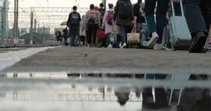A multidão de povos que andam em sentidos diferentes com bagagem, cobre abaixo do tiro dos povos, muitos povos com sacos e grande filme