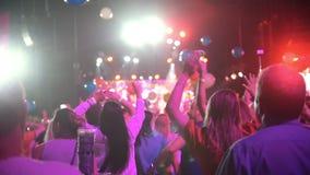 Multidão de povos que dançam que levanta as mãos em um concerto - balões multi-coloridos que voam em torno da sala de concertos video estoque