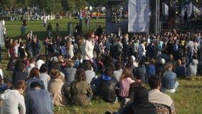 Multidão de povos que sentam-se na observação da grama filme