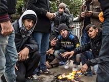 Multidão de refugiados que esperam dentro de um fogo em uma manhã fria do inverno para registrar e entrar na Sérvia na beira com  fotos de stock royalty free