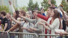 A multidão dos jovens move as mãos ritmicamente no concerto exterior da música do verão video estoque
