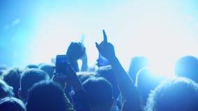 Multidão em luzes das mãos do aplauso do concerto, dança, tomando fotos com smartphones filme