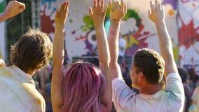 Multidão feliz que aprecia o desempenho no festival exterior, saltando com mãos acima vídeos de arquivo