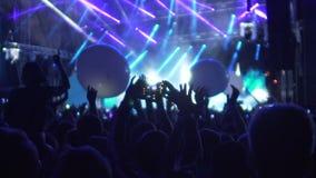 Multidão feliz que joga com os balões enormes no concerto, aplaudindo à faixa popular filme