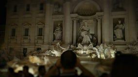 A multidão na frente da fonte do Trevi, um homem dispara em uma fonte na noite de Roma do smartphone filme