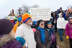 A multidão na reunião guarda sinais enquanto os estudantes chegam Fotografia de Stock