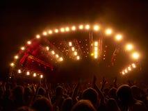 Multidão no concerto de rocha na frente da fase iluminada Imagem de Stock Royalty Free