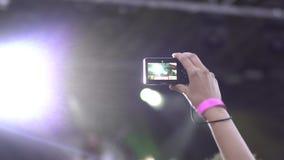 Multidão que partying no concerto de rocha do ar livre Posição da jovem mulher no smartphone da terra arrendada da multidão nas m vídeos de arquivo