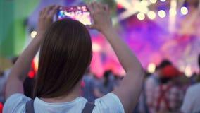 Multidão que partying no concerto de rocha do ar livre Posição da mulher, smartphone da terra arrendada nas mãos que disparam no  vídeos de arquivo