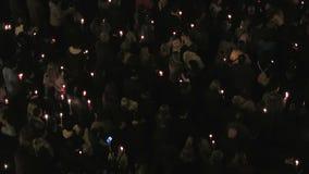 Multidão recolhida que guarda velas na noite vídeos de arquivo
