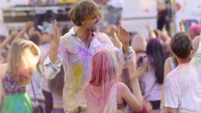 Multidão selvagem que vai louca no festival fresco, amigos cobertos na pintura que toma o selfie video estoque