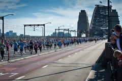 Multidões que correm na estrada através de Sydney Harbour Bridge para uma corrida do divertimento fotografia de stock royalty free