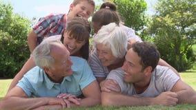 MultidieGeneratiefamilie omhoog in Tuin samen wordt opgestapeld stock footage