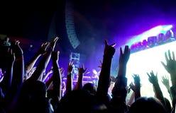 Multidão de povos em um concerto de rocha com mãos no ar Fotografia de Stock Royalty Free