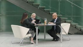 Corporate executives meeting in lobby of modern office building. Multiehnic corporate executive team meeting in company office discussing business