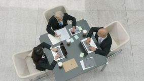 High angle view of three corporate business people meeting in office