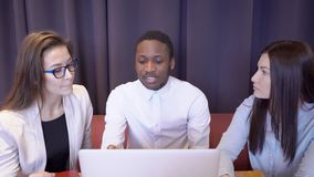 Multiethical team Novice businessmen talking while sitting at table with laptop in restaurant. African man. Tells two women about new project, gesticulating stock footage