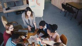 Multiethnic δημιουργικό 'brainstorming' ομάδων τοπ άποψης στο καθιερώνον τη μόδα σύγχρονο coworking γραφείο Ο θηλυκός προϊστάμενο απόθεμα βίντεο