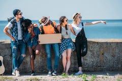 multiethnic νέοι φίλοι με την κιθάρα και το κενό χαρτόνι που δείχνουν μακριά ενώ Στοκ Εικόνα