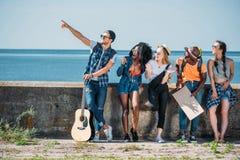 multiethnic νέοι φίλοι με την κιθάρα και το κενό χαρτόνι που δείχνουν μακριά ενώ Στοκ Εικόνες