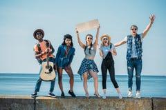 multiethnic νέοι φίλοι με το κενό χαρτόνι που στέκεται στο στηθαίο ενώ Στοκ Εικόνες
