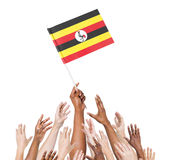 Multiethnic Arms Raised for the Flag of Uganda Stock Photo