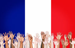 Multiethnic Arms Raised Up on a Flag of France Royalty Free Stock Image