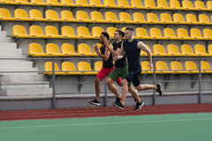 Multiethnic athlete group run on running track outdoors Royalty Free Stock Images