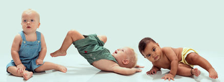 Multiethnic babies. Dancing on light background stock photo