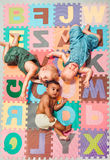 Multiethnic babies. Lying around on Alphabet puzzle background royalty free stock photo