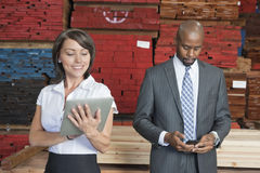 Multiethnic business colleagues using tablet PC and cell phone with stacked wooden planks in background Stock Photography