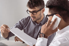 Multiethnic business partners negotiating agreements and talking on smartphone. Young multiethnic business partners negotiating agreements and talking on Stock Images