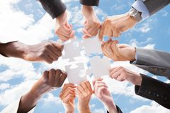 Multiethnic business people assembling jigsaw puzzle against sky. Directly below shot of multiethnic business people assembling jigsaw puzzle against sky royalty free stock photography