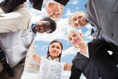 Multiethnic Business People Forming Huddle Against Sky royalty free stock images