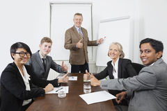 Multiethnic business people giving thumbs up in meeting Stock Images