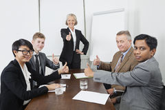 Multiethnic business people giving thumbs up in meeting Royalty Free Stock Image