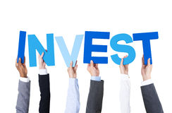 Multiethnic Business People Holding Word Invest Stock Images